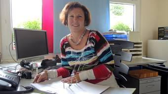 Claudia Bieri sitzt mit einem lachenden und weinenden Auge vor dem GREWA-Ordner in ihrem Büro.