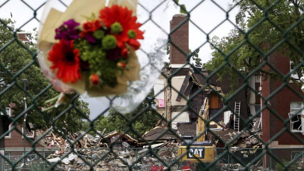 Blumen stecken in einem Zaun bei der Privatschule in Minnehaha, wo sich eine tödliche Gasexplosion ereignete.