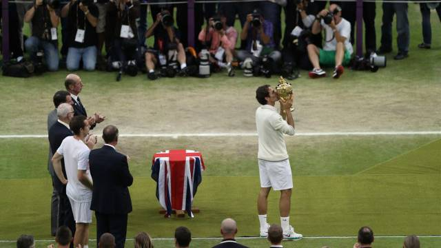 Roger Federer erhält letzten Sonntag seine 7. Wimbledon-Trophäe, nach dem Finalsieg gegen Andy Murray. Foto: Clive Rose