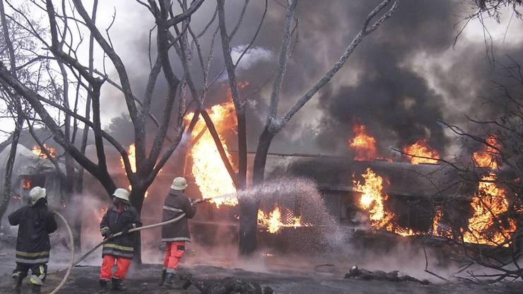 Nach der Explosion eines Tanklastwagens bekämpfen Feuerwehrleute den Brand.