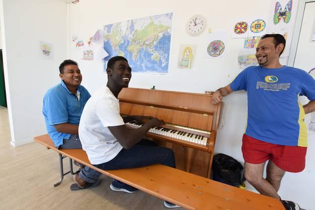 Nando* aus dem Sudan versucht sich am Klavier, Rajah* aus Sri Lanka (l.) und der Serbe Dejan* (r.) helfen ihm.