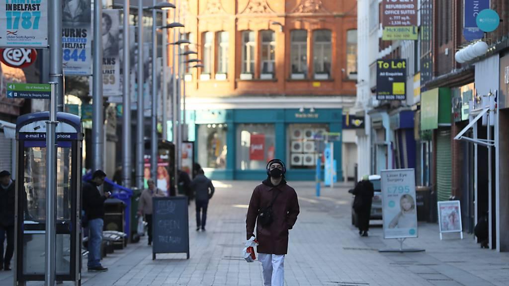 dpatopbilder - Ein Mann geht in einer Straße an geschlossenen Geschäften vorbei. Nordirland befindet sich in einem sechswöchigen Lockdown aufgrund der Corona-Pandemie. Foto: Brian Lawless/PA Wire/dpa