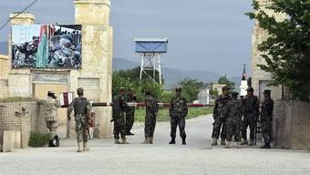 Soldaten bewachen den Eingang zum angegriffenen Militärgelände: Mindestens 50 afghanische Soldaten sollen durch die Taliban getötet worden sein.