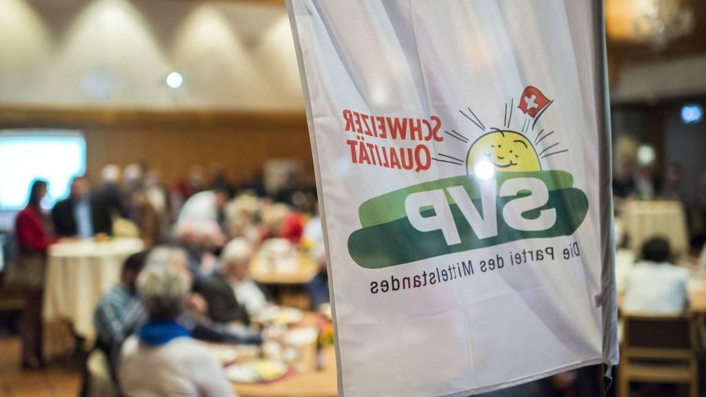 Eine Fahne und Mitglieder der SVP während der Wahlveranstaltung im Restaurant Roessli in Ilnau-Effretikon am Sonntag, 18. Oktober  2015. (KEYSTONE/Dominic Steinmann)
