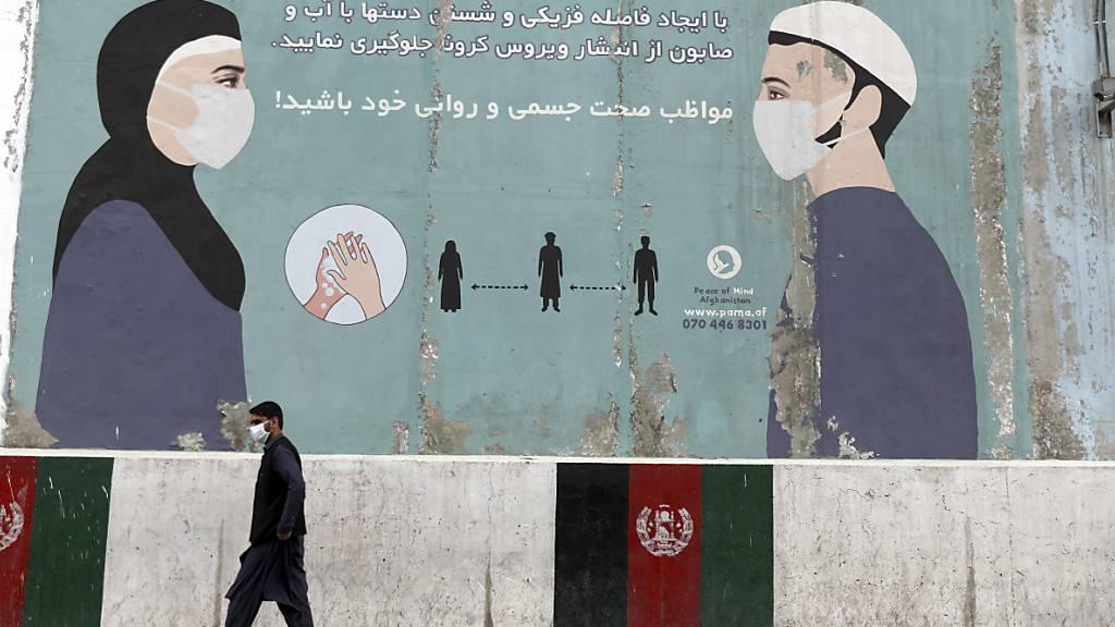 Ein Passant geht in der afghanischen Hauptstadt an einer bemalten Wand vorbei, auf der auf die coronabedingten Hygieneregeln hingewiesen wird. Zuletzt hat das Land mehr Corona-Tote binnen eines Tages verzeichnet als je zuvor. Foto: Rahmat Gul/AP/dpa