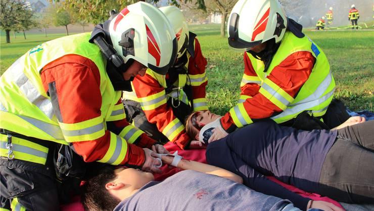 Gerettet: Die Sanität versorgt die Verletzten etwas abseits vom Einsatz der Feuerwehr, welche das Feuer bekämpft. Carolin Frei