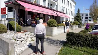 Gestern Nachmittag um 14 Uhr: Kunden (und auch Begleitende) warten in gebührendem Abstand voneinander vor der Metzgerei Fischer in Langendorf darauf, dass sie das  Geschäft betreten und ihre Waren einkaufen können.