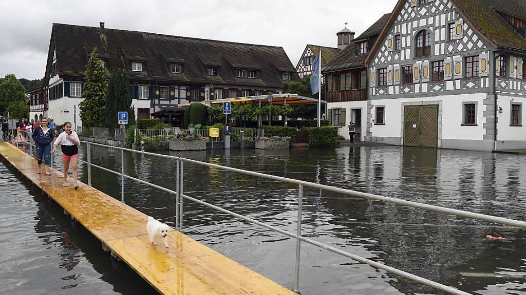 Menschen gehen über einen Notsteg in Ermatingen TG (Bild vom Sonntag, 19. Juni 2016). Der Bodensee stieg am Montag nochmals um einige Zentimeter an. Der Höchststand des Hochwassers dürfte aber erreicht sein.