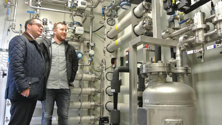 Philippe Lehmann (Projektleiter Regionalwerke Baden, rechts) erklärt Stadtrat Roger Huber, Präsident des Abwasserverbandes Region Baden Wettingen und damit Grundeigentümer, wie das Rohgas in der Biogasaufbereitungsanlage veredelt und ins Erdgasnetz eingespeist wird.