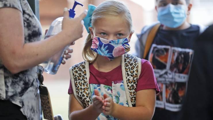 Schutzmaske und Desinfektionsmittel gegen das Virus: eine Schülerin im texanischen Godley bereitet sich auf den Unterricht vor .
