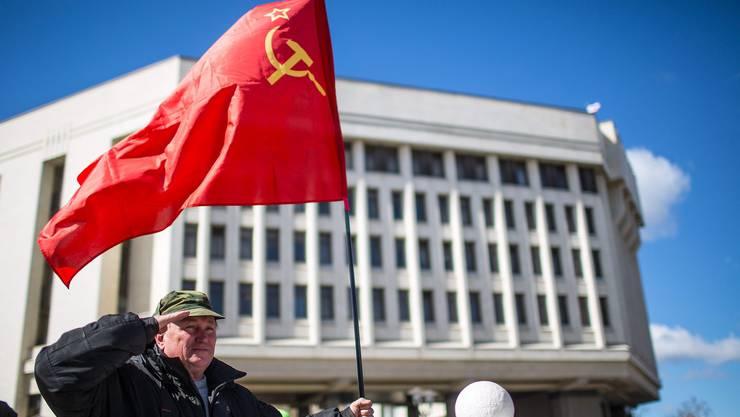 Ein Mann hält eine Sowjet-Flagge vor dem Parlament in Simferopol.
