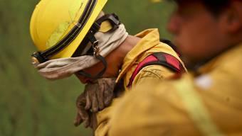 Chilenische Feuerwehrmänner bei einer Verschnaufpause in ihrem Kampf gegen die Brände