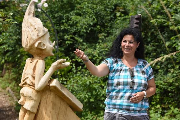 Daniela Grieder, Zuständige für das Ressort Kultur im Bürgerrat Reinach, betrachtet die Figur, die beim Eingang des Holzskulpturenweg steht