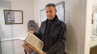 Rolf Bolliger zeigt die Disputation, die im Dorfmuseum ausgestellt ist.