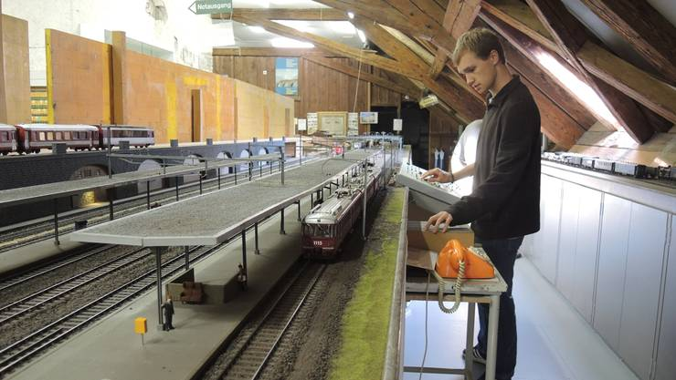 Christof Perren bedient die Bahnanlage im Dachstock. Neben dem Bahnhof befindet sich eine Eisenbahnlandschaft.
