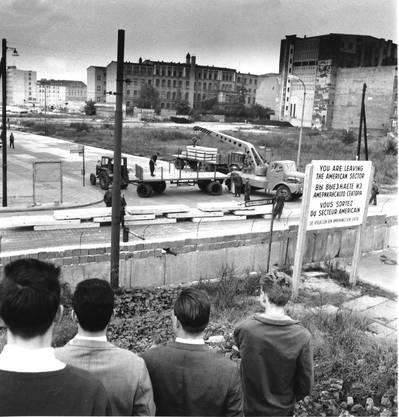 Westberliner schauen am 12. September 1961 an der Wilhelmstrasse in Berlien der Anlieferung vorgefertigter Betonbauteile zur Verstärkung der Berliner Mauer zu.