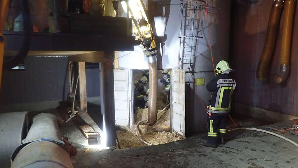 Feuerwehrleute löschen den Mottbrand in diesem Holzschnitzelsilo in einem Gewerbebetrieb in Oberhofen TG.