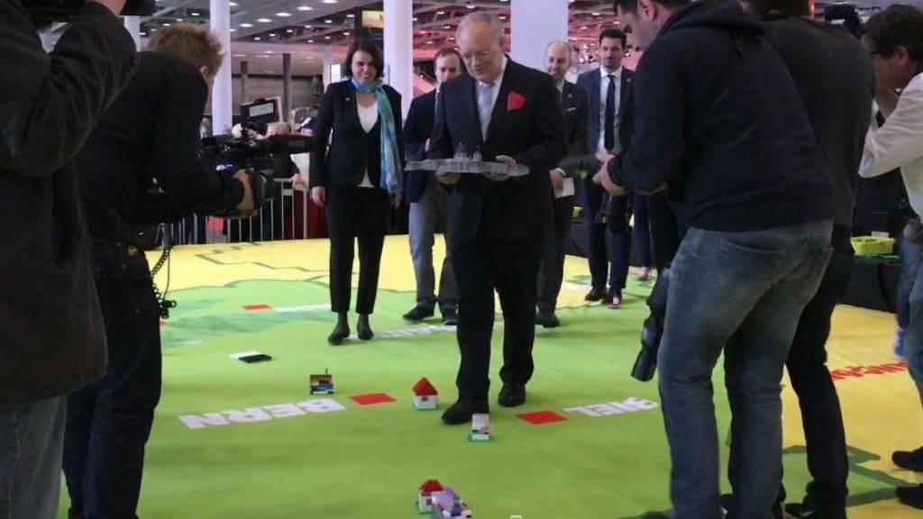 Bundesrat Johann Schneider-Ammann setzt an der muba-Eröffnung in Basel ein Lego-Bundeshaus auf eine Schweizer Karte.