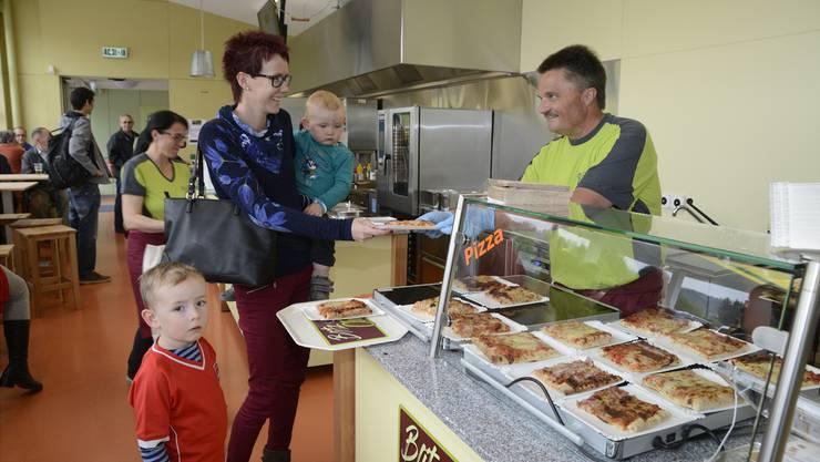 Jörg Eggimann hatte gestern alle Hände voll zu tun. Hier reicht er Pizzen für Tamara Marti aus Lohn mit Louis (auf dem Arm) und Flynn über die Theke.