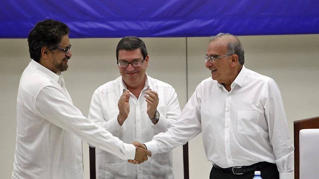 Die Chefs der beiden Verhandlungsdelegationen schütteln sich im Beisein des kubanischen Aussenministers Bruno Rodriguez nach ihrer Einigung über ein Friedensabkommen die Hände. Kolumbiens Regierung und die FARC-Rebellen verhandelten fast vier Jahre lang.