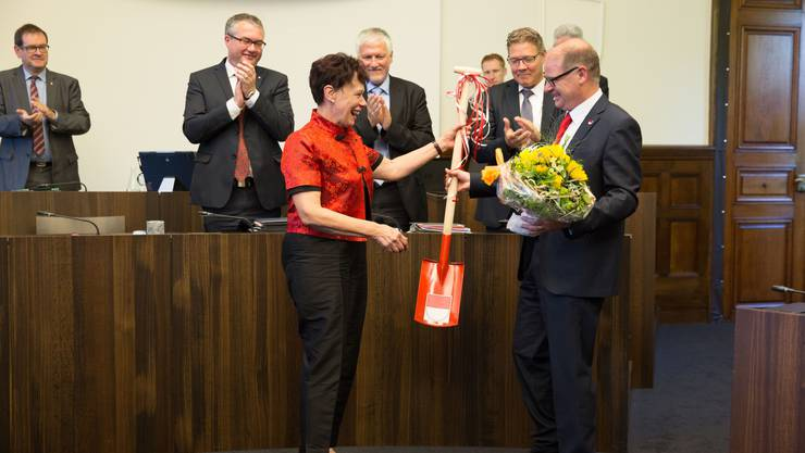 Esther Gassler bekommt eine rote Schaufel und Blumen von Kantonsratspräsident Urs Huber.