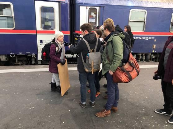 """Im Gepäck: ein Rucksack, ein kleiner roter Koffer und ein Demonstrationsschild mit der Aufschrift """"Skolstrejk for klimatet"""" (Schulstreik fürs Klima)."""