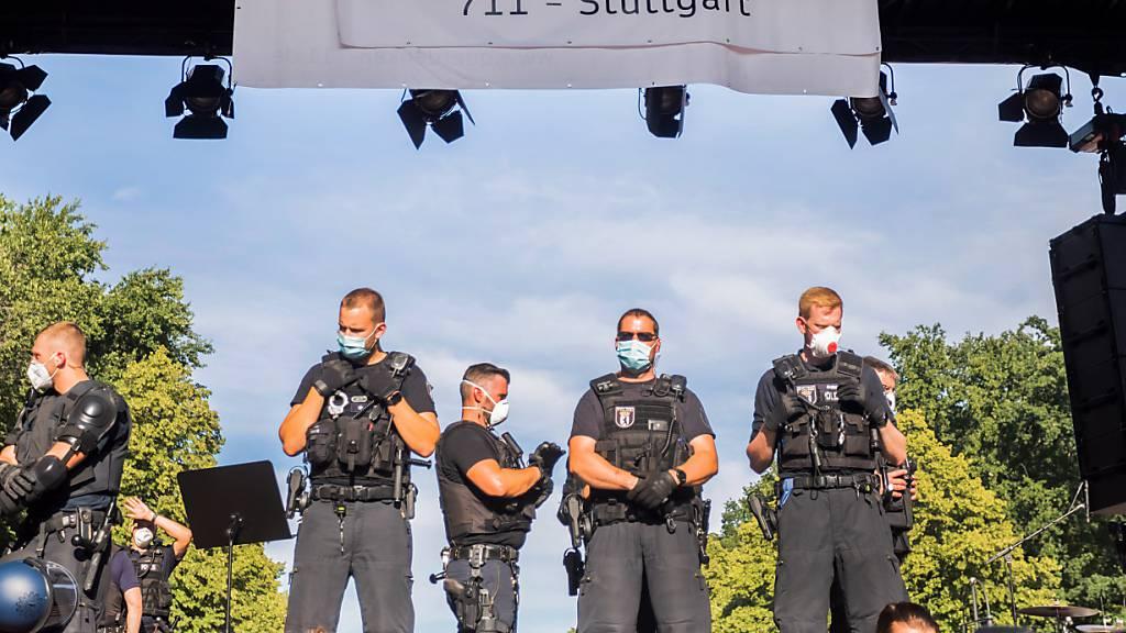 ARCHIV - Polizisten stehen bei einer Kundgebung gegen die Corona-Beschränkungen auf der Straße des 17. Juni auf der Bühne unter dem Banner der Initiative «Querdenken 711». Die Polizei hatte die Veranstaltung aufgelöst. Foto: Christoph Soeder/dpa