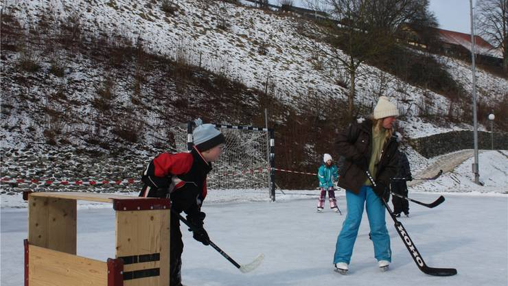Kinder und Erwachsene aus dem Dorf vergnügen sich auf dem Eis MCE