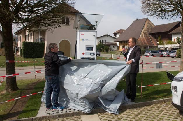 Der Bremgarter Stadtrat Daniel Sommerhalder (links) und Markus Wey, Präsident der Elektrizitätsgenossenschaft, enthüllen die Ladestation.