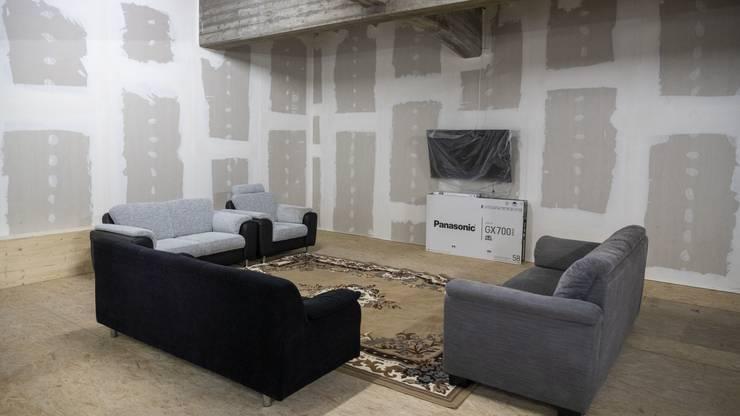 So sieht der Aufenthaltsraum mit Sofa und Fernseher aus.