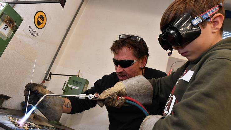 Noël Ruben schmelzt Messing für seine Form. Werklehrer Michael Bielser hilft dabei.