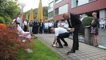 Vorstandspräsident Mike Lauper setzt feierlich den ersten gravierten Stein ins «Ehregässli», den neuen Walk of Fame der Oberen Mühle.