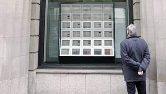 Ein Passant studiert die Aktienkurse in Zürich (Archiv)