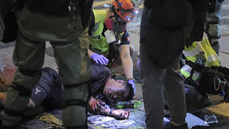 Wurde von Demonstranten in Hongkong attackiert: Medizinpersonal kümmert sich um einen verletzten Mann am Boden.