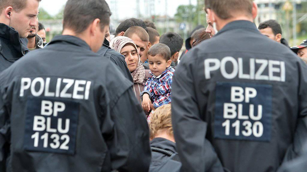 Deutsche Polizisten registrieren Flüchtlinge nach deren Ankunft - die Grenzkontrollen stossen in den USA auch auf Verständnis.