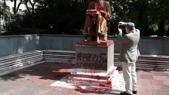 Ein Mann fotografiert die von Demonstranten mit roter Farbe beworfene Statue des verstorbenen italienischen Journalisten Indro Montanelli in Mailand. Foto: Antonio Calanni/AP/dpa