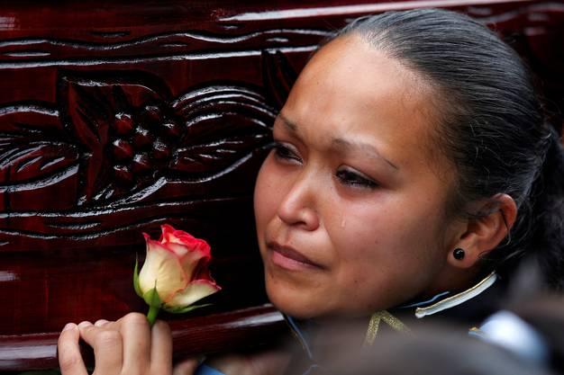 Die Studentin weint, als sie den Sarg ihres Klassenkameraden trägt.