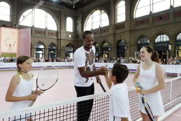 Der franzoesische Tennisprofi Gael Monfils rechts, klatscht mit Kindern ab.