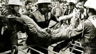 Feuerwehrmänner und Sanitäter helfen einem Opfer des Unglücks von 1985 (Archiv)