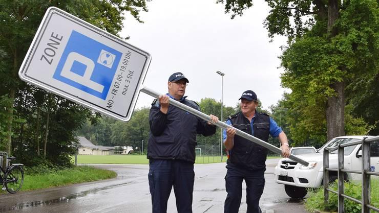 Heiner Hossli, Chef der Regionalpolizei Brugg (links), bringt mit seinem Kollegen Walter Huber die neue Signalisationstafel zum Standort am Brückengeländer