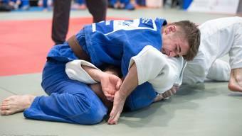 Adam Batsiev (in Blau) gewinnt mit einem Sieg durch Festhalter gegen einen vermeintlich stärkeren Gegner.