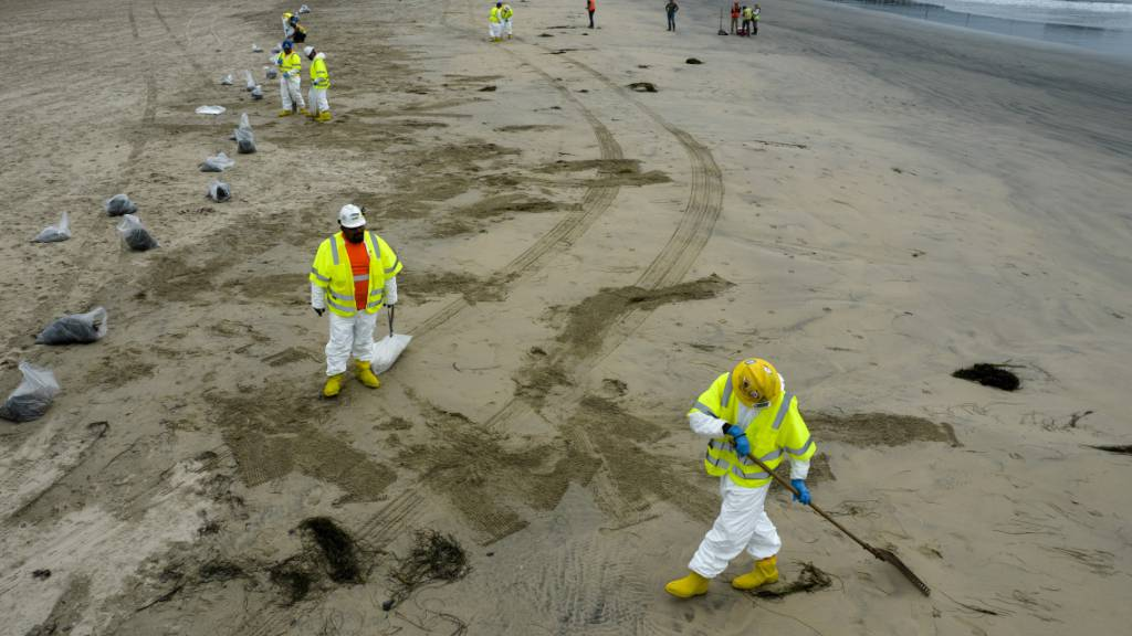 Arbeiter in Schutzanzügen säubern einen vom ausgetretenen Öl verunreinigten Strand in Newport Beach in Kalifornien. Foto: Ringo H.W. Chiu/AP/dpa