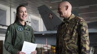 epa07380821 Fanny Chollet (L), the first female fighter pilot of the Swiss Air Force, smiles in front of a F/A-18 Hornet fighter jet during a press conference with Divisional General Bernhard Mueller (R), Commander of the Swiss Air Force, at the Swiss military base in Payerne, Switzerland, 19 February 2019. Swiss Air Force 1st Lieutenant Chollet, 28, nicknamed 'Shotty', reportedly is the first woman in Switzerland to fly a fighter jet and the first female F/A-18 pilot outside North America. EPA/LAURENT GILLIERON
