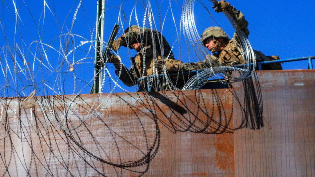 Amerikanische Soldaten verstärken den Grenzzaun zwischen den USA und Mexiko. Am Dienstag versuchten etwas 20 Migranten den Zaun zu erklettern. (Foto: Joebeth Terriquez/EPA)