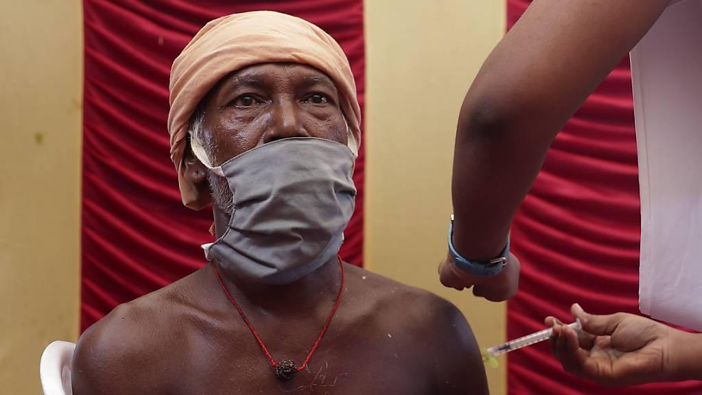 Ein Mitarbeiter des indischen Gesundheitswesens impft einen Mann. Angesichts deutlich sinkender Infektionszahlen wagen die Millionenstädte Delhi und Mumbai zusammen mit weiteren Regionen nun erste Lockerungen.