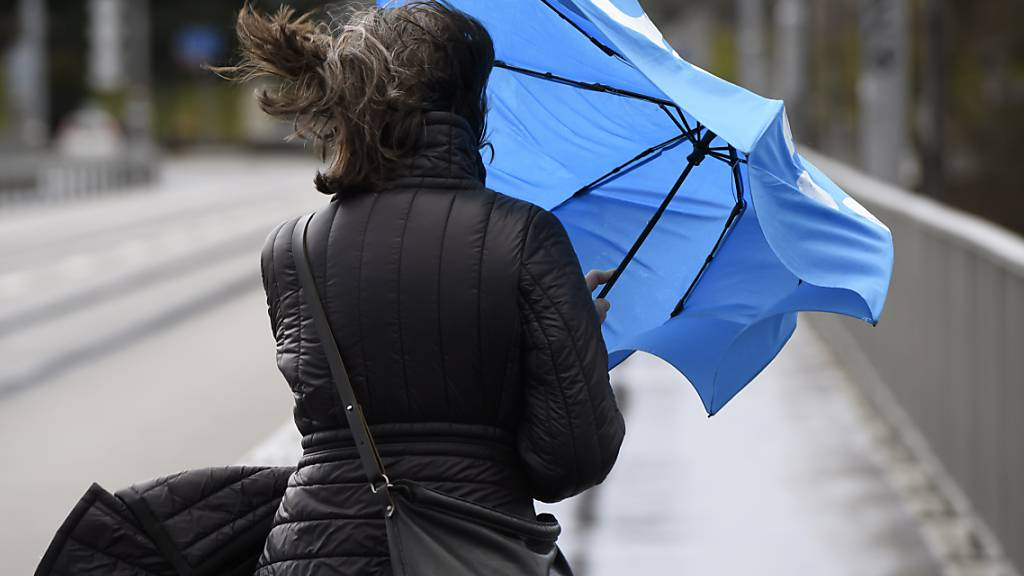 Stürmische Winde und viel Regen: Eine Frau kämpft mit den Tücken des Wetters. (Symbolbild)