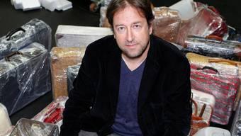 Theaterintendant Georges Delnon sitzt auf gepackten Koffern.