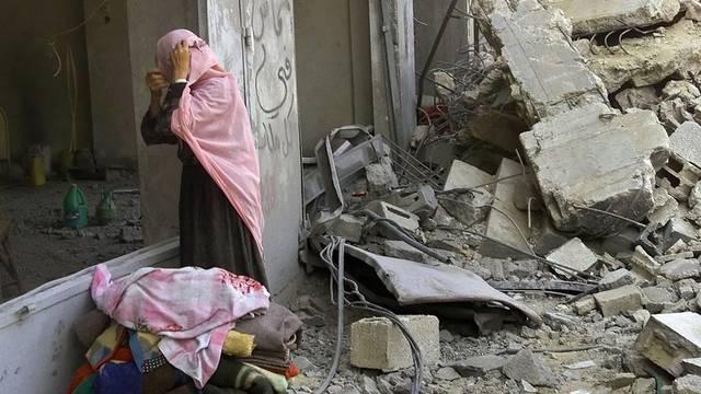 Eine palästinensische Frau holt Decken aus ihrem Haus, das beim Angriff am 22. Juli 2002 zerstört wurde (Archiv)