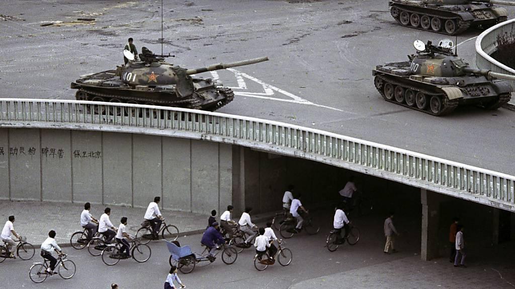 ARCHIV - Zwei Tage nach dem Massaker auf dem Tiananmen-Platz in Peking radeln Pendler durch einen Tunnel, während oben auf der Überführung Militärpanzer stehen. Hongkong hat eine jährliche Mahnwache für die Opfer der blutigen Niederschlagung der Protestbewegung auf dem Platz des Himmlischen Friedens am 4. Juni 1989 in Peking erneut verboten und ein dem Ereignis gewidmetes Museum geschlossen. Foto: Vincent Yu/AP/dpa