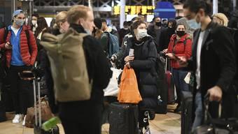 Reisende warten am letzten Samstag vor Weihnachten in der Bahnhofshalle der Londoner Paddington Station. Foto: Stefan Rousseau/PA/dpa